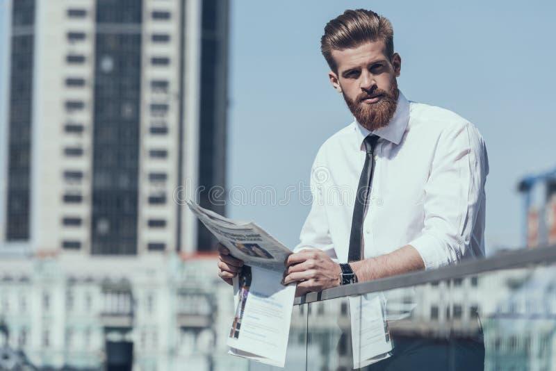 Ernster Geschäftsmann Reading Newspaper Outdoor stockfoto