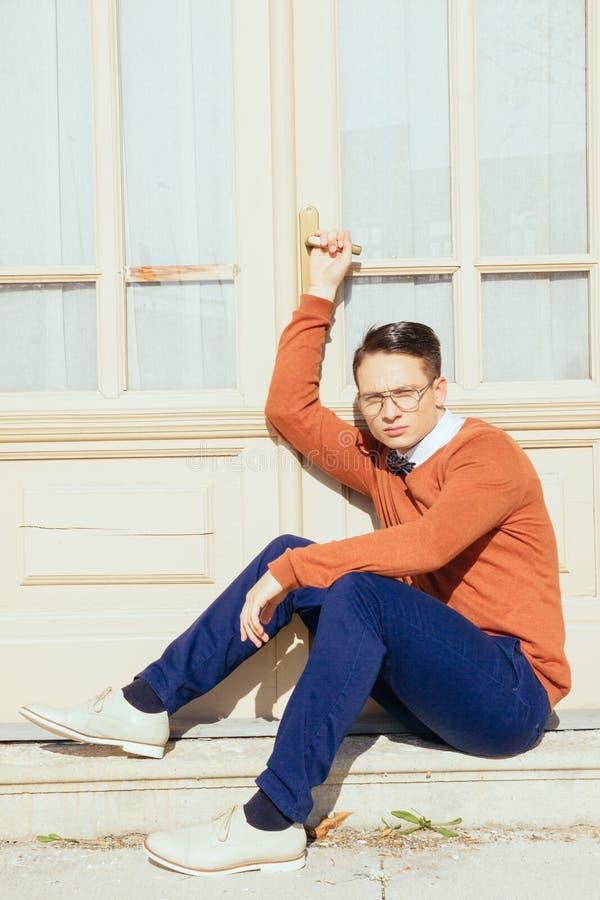 Ernster gutaussehender Mann mit den Gläsern und Strickjacke, die auf Schritten I sitzen stockfotografie