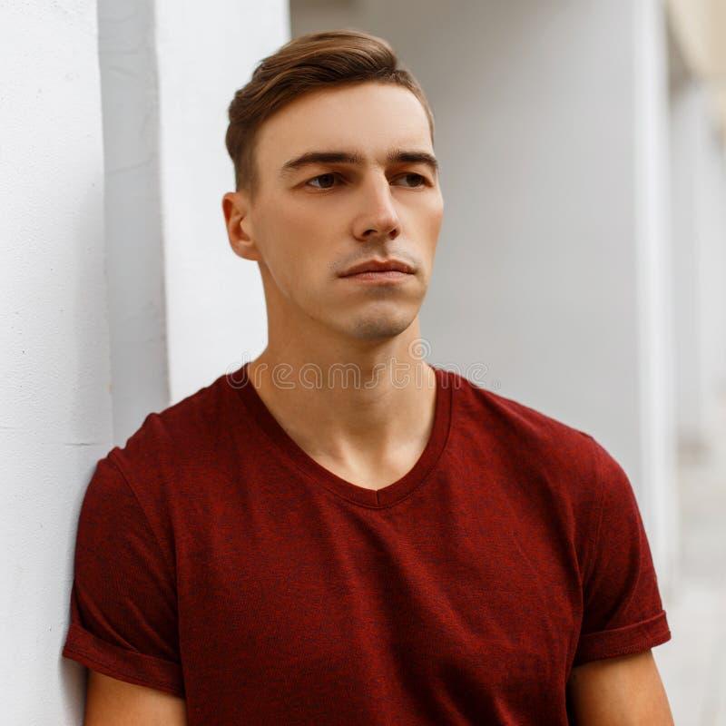 Ernster hübscher junger Mann in einem modernen roten T-Shirt mit einer stilvollen Frisur steht draußen lizenzfreie stockfotos