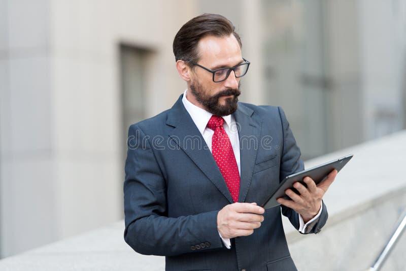Ernster Immobilienmakler, der seine Tablette und Denken betrachtet lizenzfreies stockfoto
