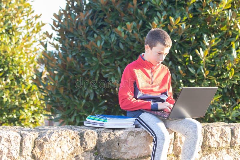 Ernster Jugendlichjunge mit dem Laptop und Lehrbüchern, die Hausarbeit tun und für eine Prüfung im Park sich vorbereiten lizenzfreie stockbilder