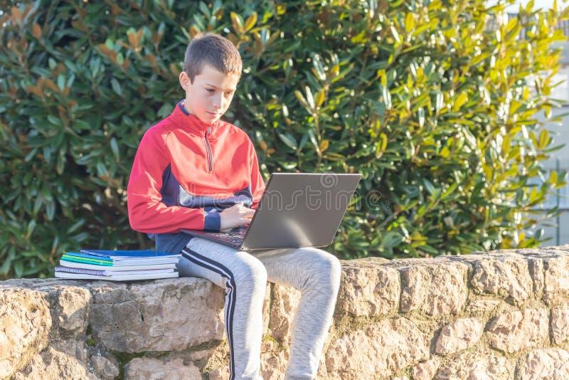 Ernster Jugendlichjunge mit dem Laptop und Lehrbüchern, die Hausarbeit tun und für eine Prüfung im Park sich vorbereiten lizenzfreie stockfotografie