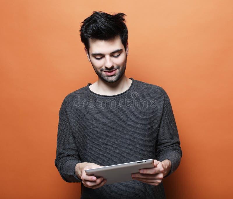 Ernster junger b?rtiger Mann unter Verwendung der digitalen Tablette gegen orange Hintergrund lizenzfreies stockbild