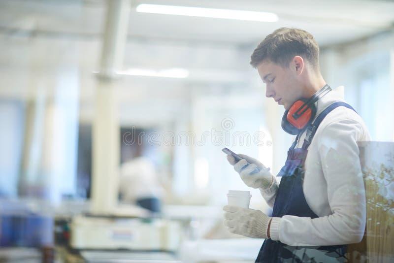 Ernster junger Bauarbeiter, der Gerät am Bruch verwendet lizenzfreie stockbilder