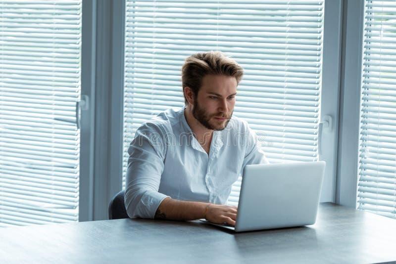 Ernster junger Geschäftsmann, der an einem Laptop arbeitet stockfotografie