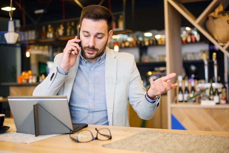 Ernster junger Geschäftsmann, der an einem Telefon, arbeitend in einem Café spricht stockfotografie