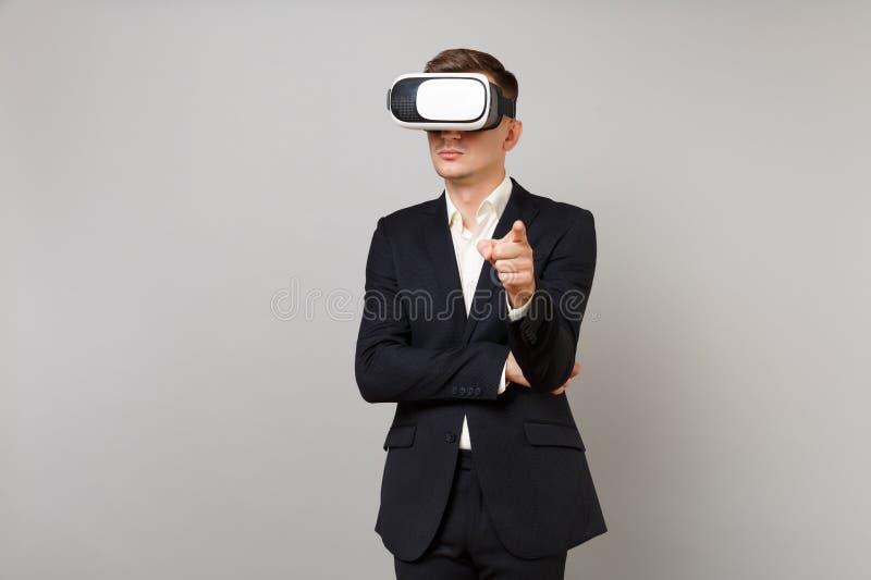 Ernster junger Geschäftsmann im klassischen schwarzen Anzug, Hemd, das im Kopfhörer, Zeigefinger auf der Kamera zeigend an lokali stockbilder