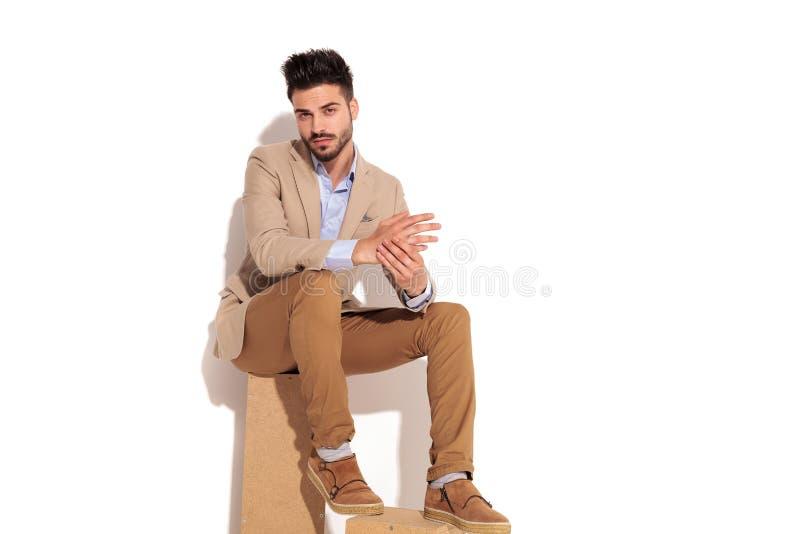 Ernster junger intelligenter zufälliger Mann, der Palmen während sitt zusammenhält lizenzfreies stockfoto