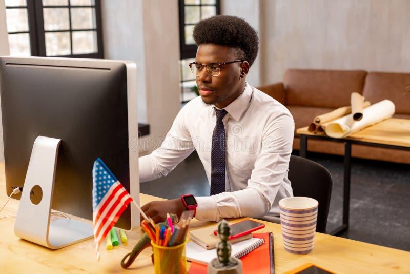 Ernster junger Mann, der den Bildschirm betrachtet lizenzfreie stockbilder