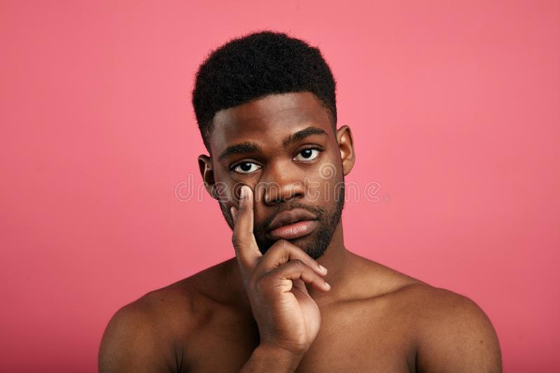 Ernster junger Mann, der durchdachten Ausdruck konzentriert wird stockbilder