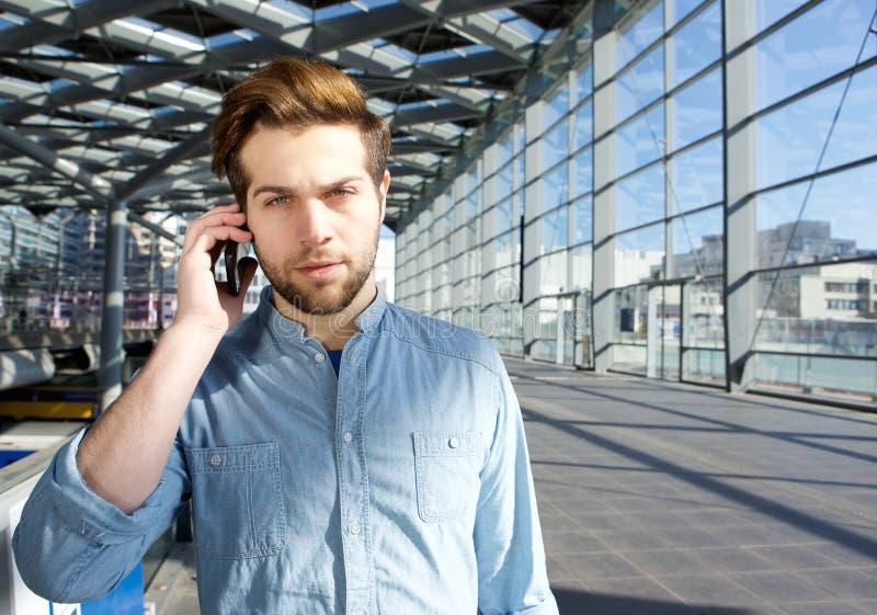 Ernster junger Mann, der am Handy innerhalb des Gebäudes spricht lizenzfreies stockbild