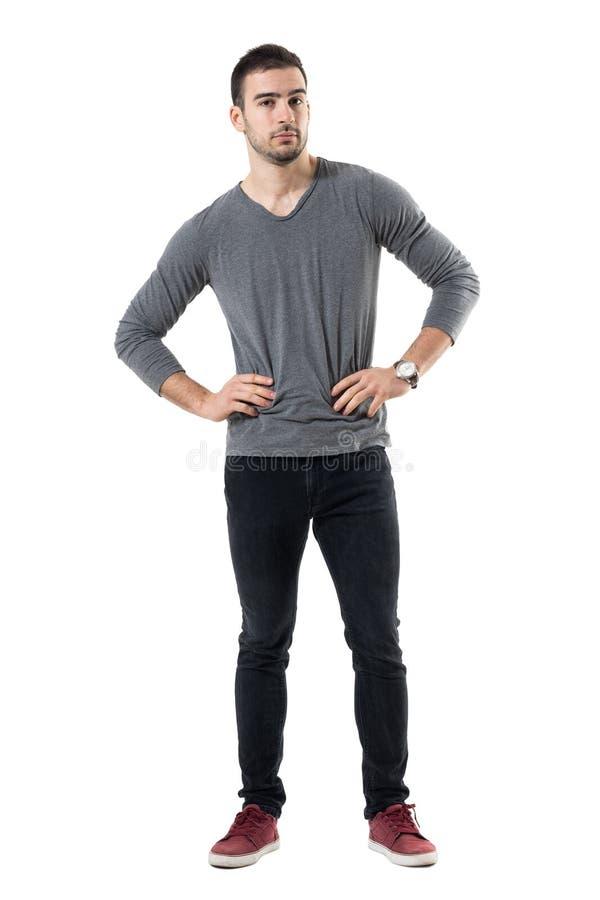 Ernster junger zufälliger Mann mit den Händen auf der Taille, die Kamera betrachtet stockfotos