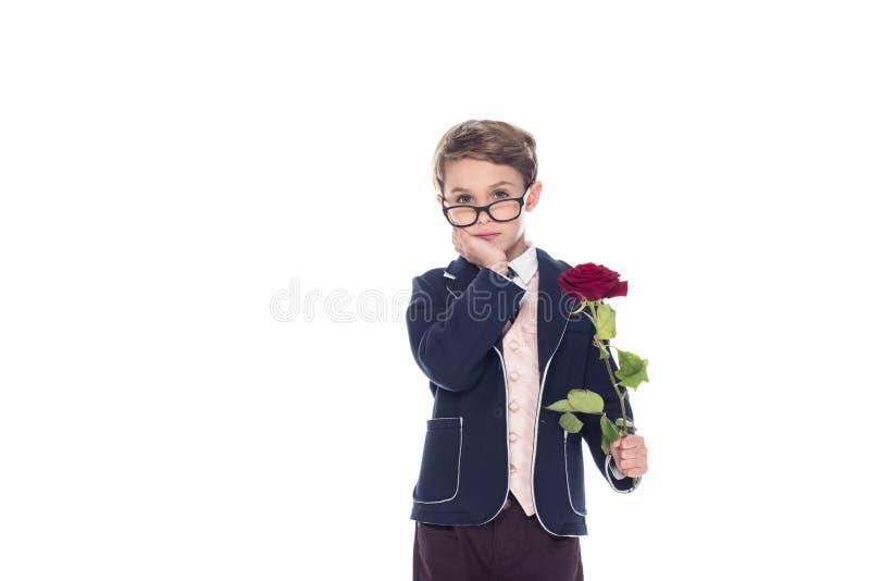 ernster kleiner Junge in der Klage und Brillen, die rosafarbene Blume halten und Kamera betrachten stockfotos