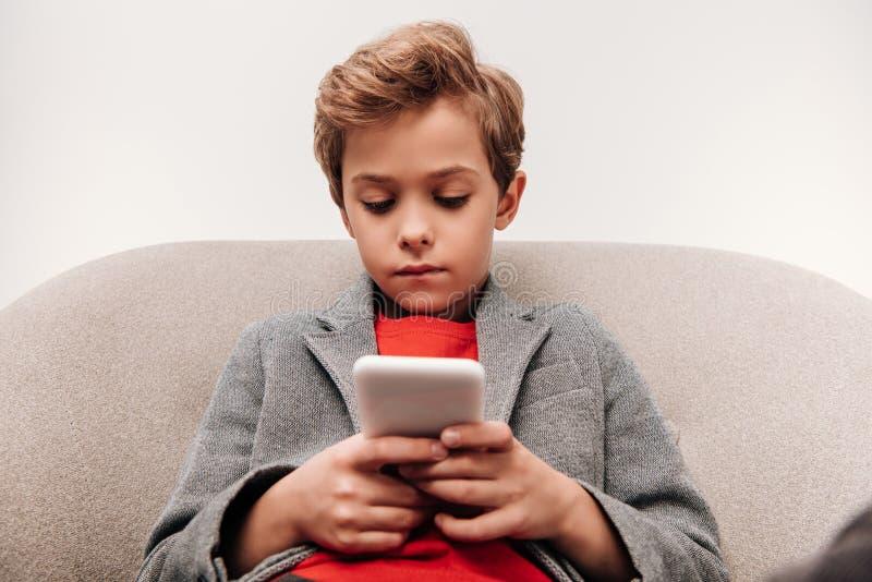 ernster kleiner Junge, der Smartphone beim Sitzen im Lehnsessel verwendet lizenzfreie stockfotografie