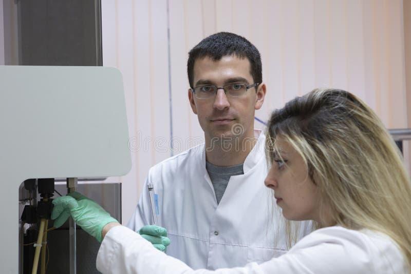 Ernster Kliniker, der chemisches Element im Arbeitsbereich studiert stockfotos