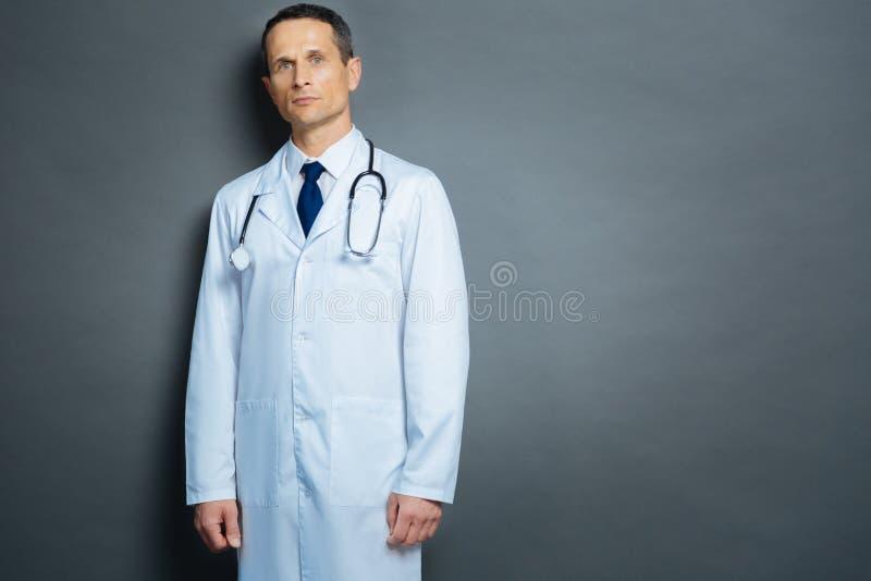 Ernster männlicher Arzt, der für Kamera über grauem Hintergrund aufwirft lizenzfreies stockbild