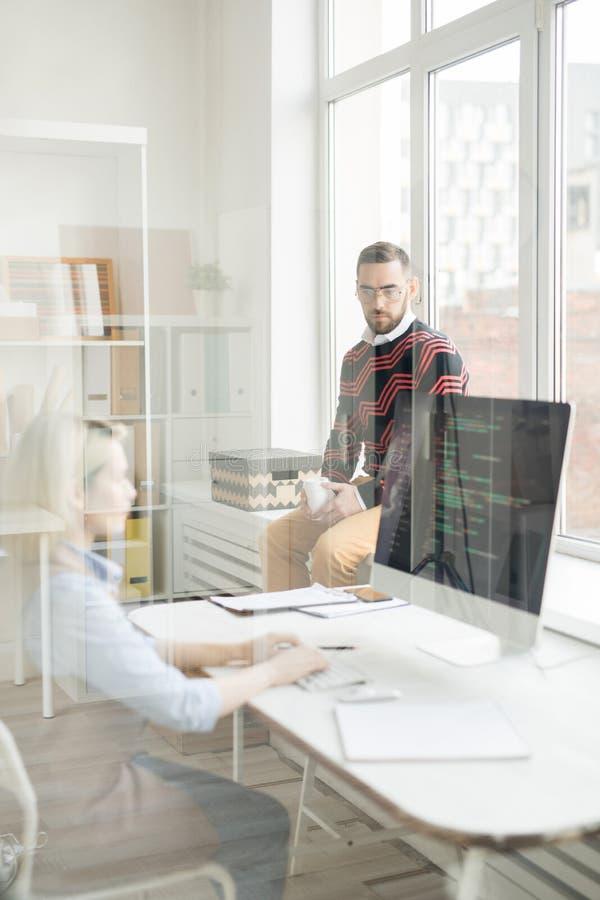 Ernster Manager, der mit Kodierer im Büro spricht lizenzfreies stockbild