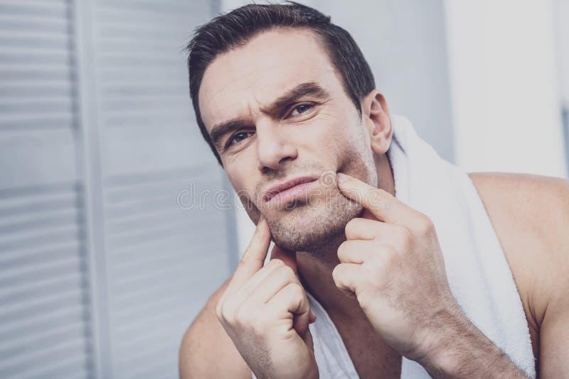 Ernster Mann, der Finger auf seinen Backen bedrängt lizenzfreies stockfoto