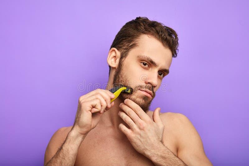 Ernster Mann, der ohne Schaum sich rasiert stockbilder