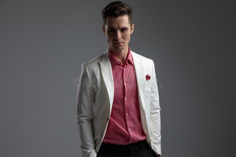 Ernster Mann in der roten Hemdstellung mit den Händen in den Taschen lizenzfreies stockfoto