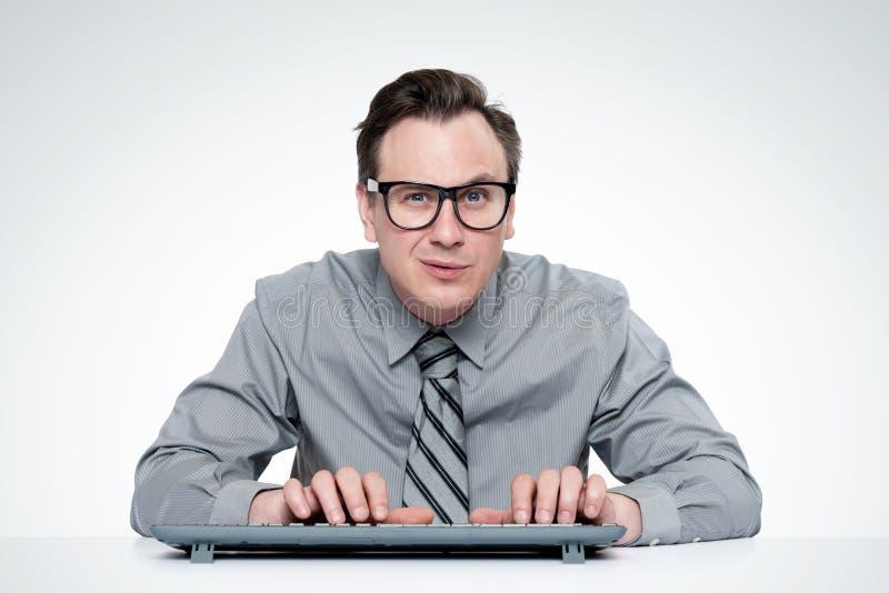 Ernster Mann in einem Hemd und Bindung, tragende Gläser, arbeitend an einem Computer, auf hellgrauem Hintergrund lizenzfreie stockbilder