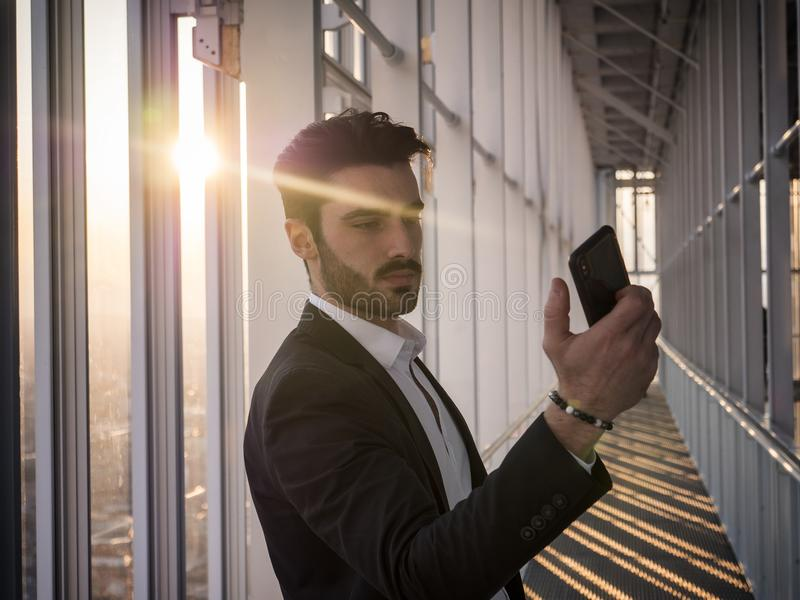 Ernster Mann im modernen Gebäude mit Handy stockbild