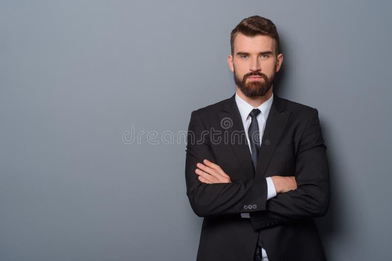 Ernster Mann mit den gekreuzten Armen lizenzfreies stockfoto