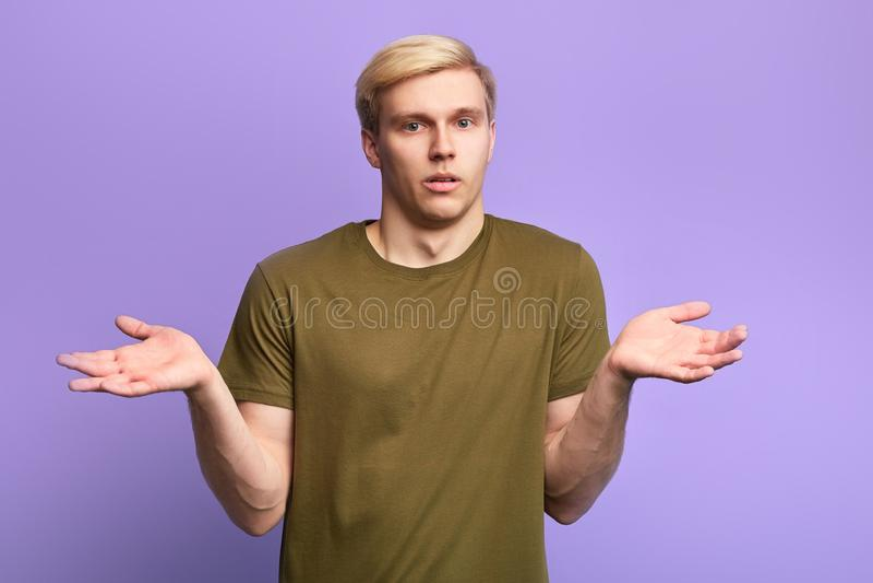 Ernster Mann mit den Händen herauf das Betrachten der Kamera lizenzfreies stockfoto
