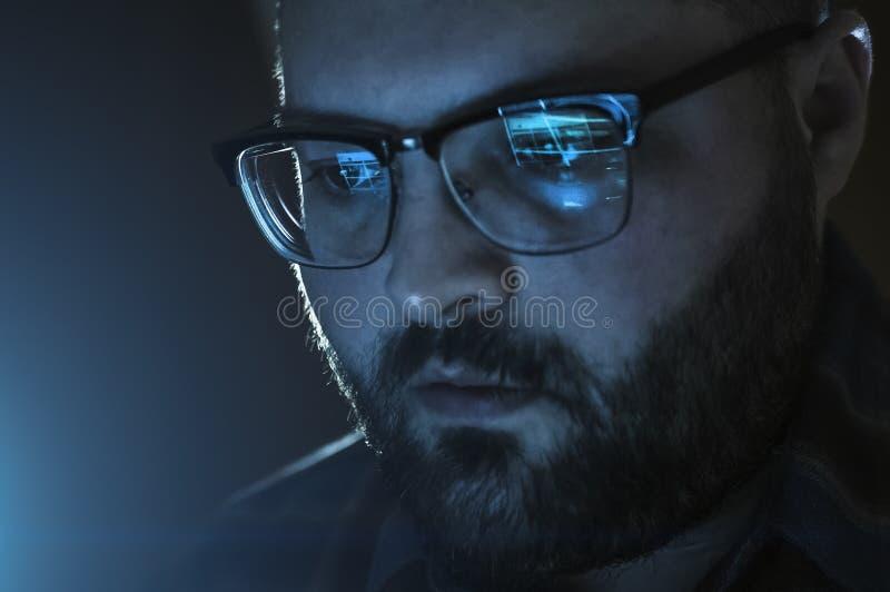 Ernster Mann mit Reflexion des Laptopschirmes mit Websitedaten, beim Glasarbeiten spät, schließen oben lizenzfreie stockfotografie
