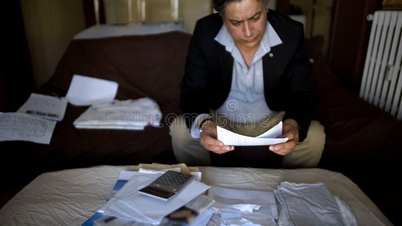 Ernster Mann niedergedrückt durch Schulden in den Wohnungsstromrechnungen, Berechnungen machend lizenzfreies stockfoto