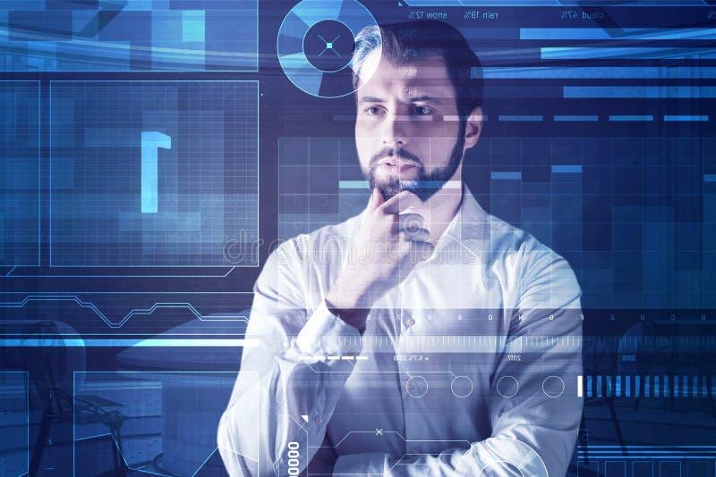 Ernster Programmierer, der seinen Bart beim Denken die Stirn runzelt und berührt stockfotografie