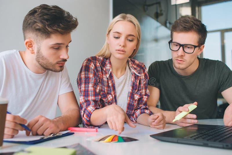 Ernster Punkt der jungen Frau auf Farbe-pallete Zwei Kerle betrachten es Mitarbeiter sitzen bei Tisch zusammen in einem Raum Sie  lizenzfreies stockbild