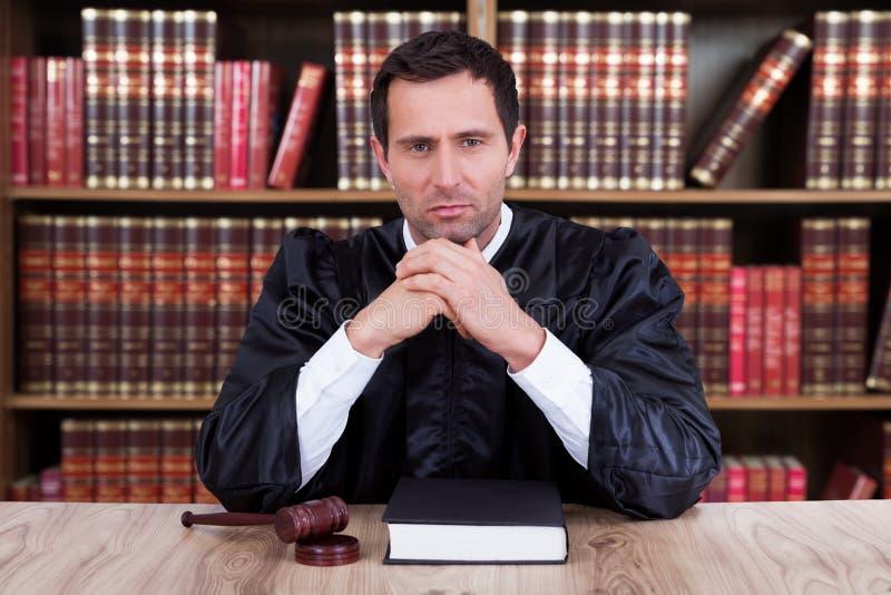 Ernster Richter Thinking While Sitting am Schreibtisch lizenzfreie stockfotos