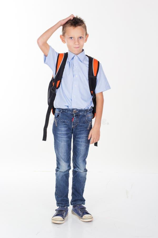 Ernster Schuljunge, der seinen Kopf verkratzt lizenzfreie stockbilder