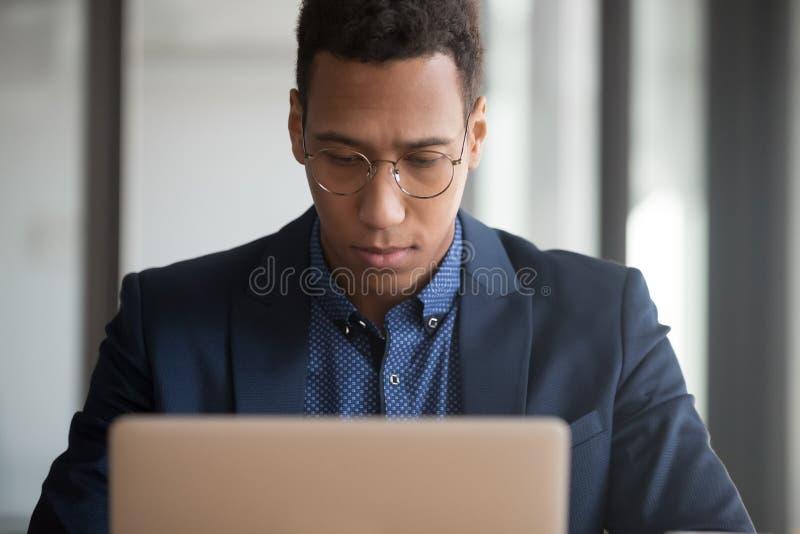 Ernster schwarzer Angestellter, der an Beratungskunden des Laptops arbeitet stockbild