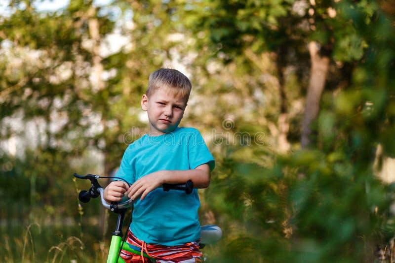 Ernster siebenjähriger Junge auf einem Fahrrad, welches die Kamera auf einem unscharfen natürlichen Hintergrund betrachtet lizenzfreie stockbilder