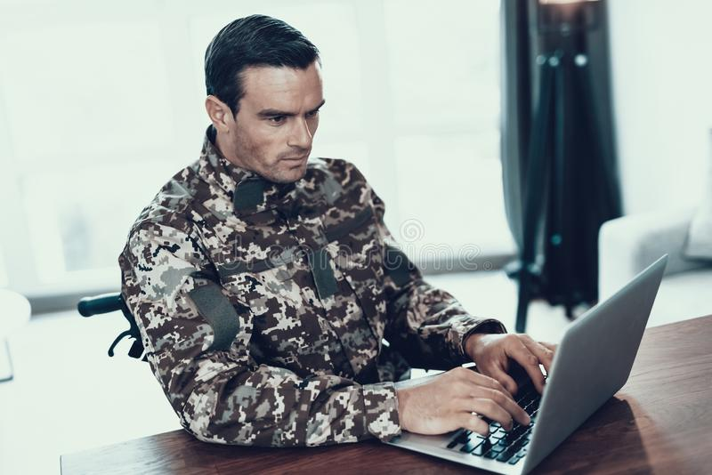 Ernster Soldat benutzt Notizbuch im Wohnzimmer stockfotografie