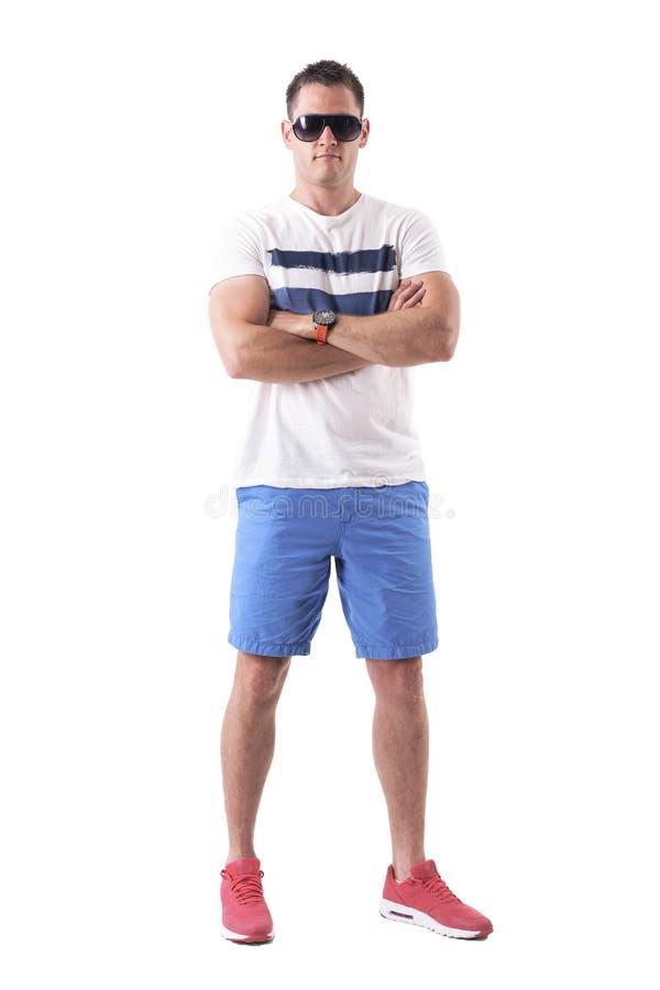 Ernster starker junger Mann kurz gesagt und Sonnenbrille mit den gekreuzten Armen stockfoto