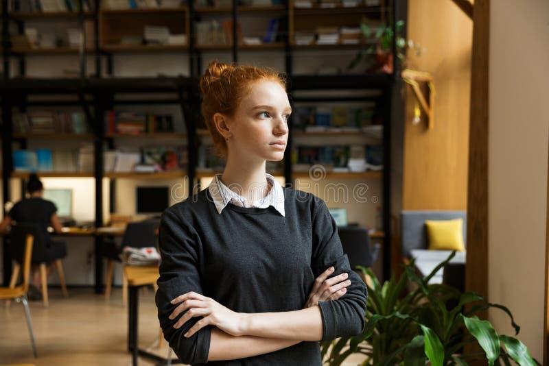 Ernster starker Rothaarigedamenstudent, der zuhause in der Bibliothek aufwirft lizenzfreie stockfotografie