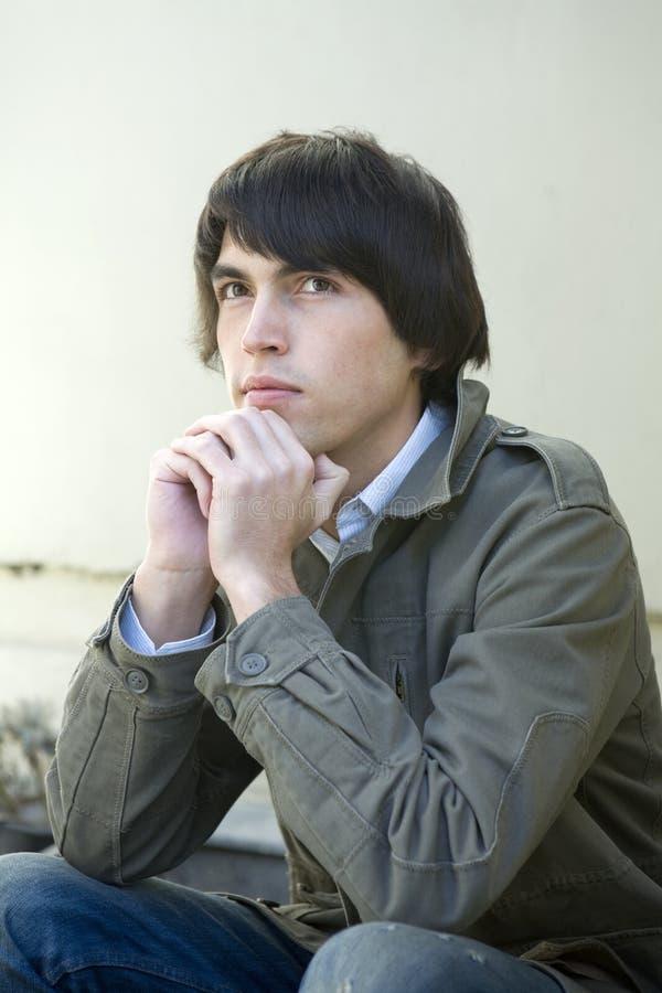 Ernster stattlicher Mann, der ein auf der Türstufe sitzt. stockfotos