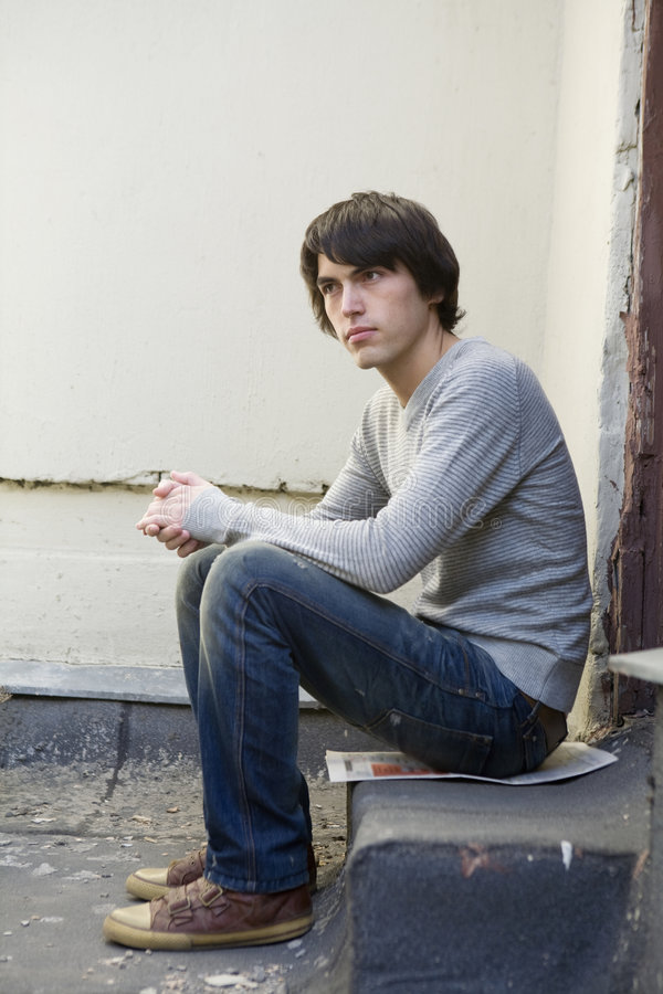 Ernster stattlicher Mann, der ein auf der Türstufe sitzt. stockfoto