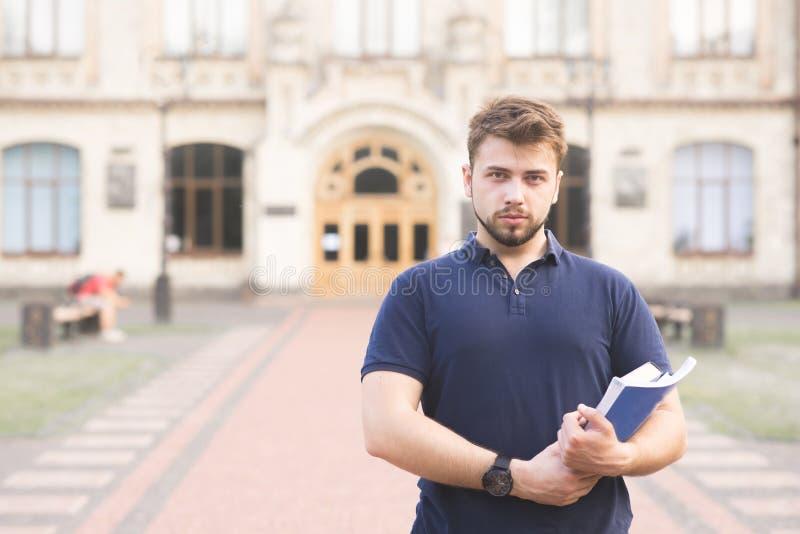 ernster Student steht mit Büchern in den Händen des Hochschulgebäudes und -blicke an der Kamera stockfoto