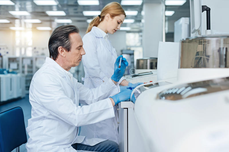 Ernster Techniker, der Blutuntersuchung tut stockbild