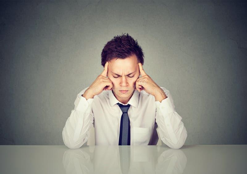Ernster trauriger betonter Mann, der bei Tisch das Denken sitzt stockbild