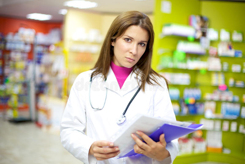 Ernster weiblicher Doktor in der Apotheke mit Dokumenten lizenzfreies stockfoto
