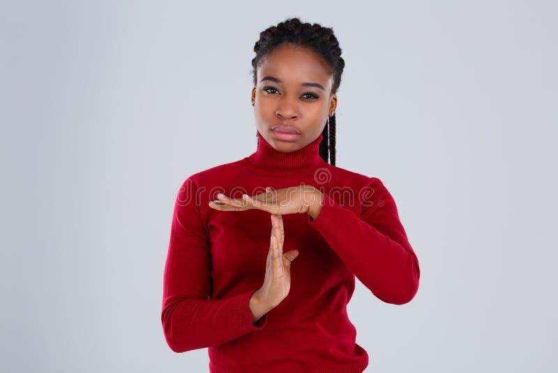 Ernstes afro-amerikanisches Mädchen, das eine Geste mit ihren Händen zeigt gegen einen grauen Hintergrund lizenzfreie stockbilder