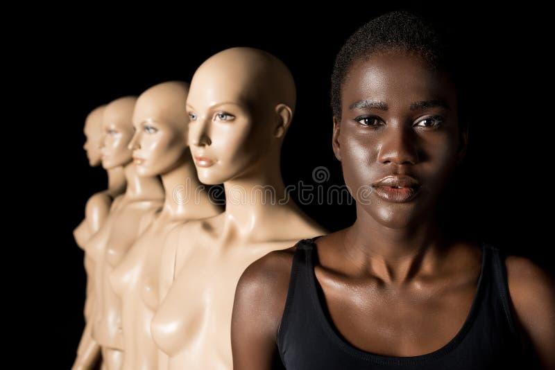 ernstes Afroamerikanermädchen, das Kamera bei der Stellung mit Attrappen betrachtet stockfotos