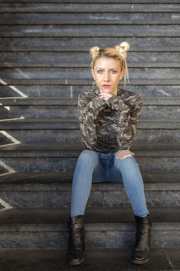 Ernstes blondes Mädchen, das auf Treppe sitzt lizenzfreie stockfotos