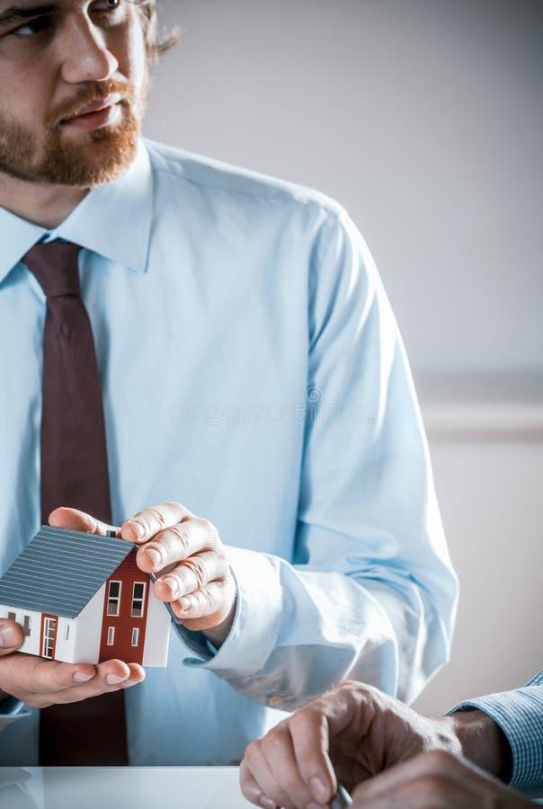 Ernstes Geschäftsmann-Holding Miniature Model-Haus stockfotos