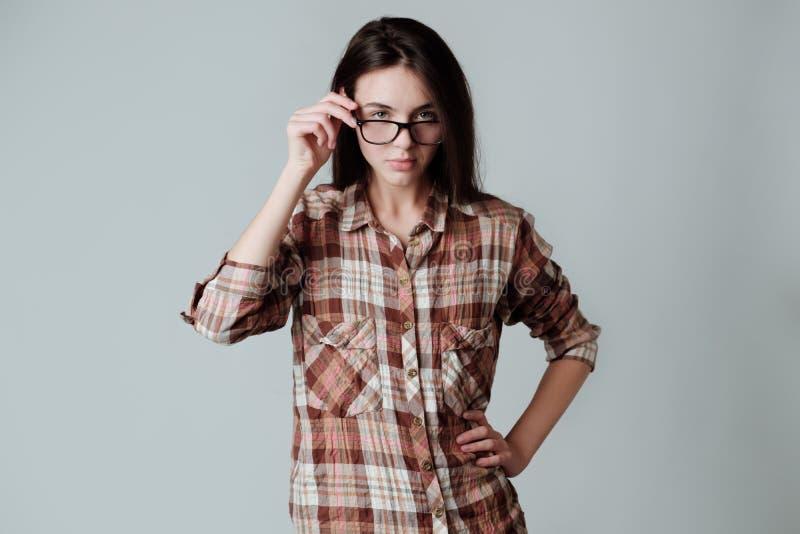Ernstes junges brunette Mädchen in lumbercheck Karohemd, das Kamera betrachtet stockfotografie